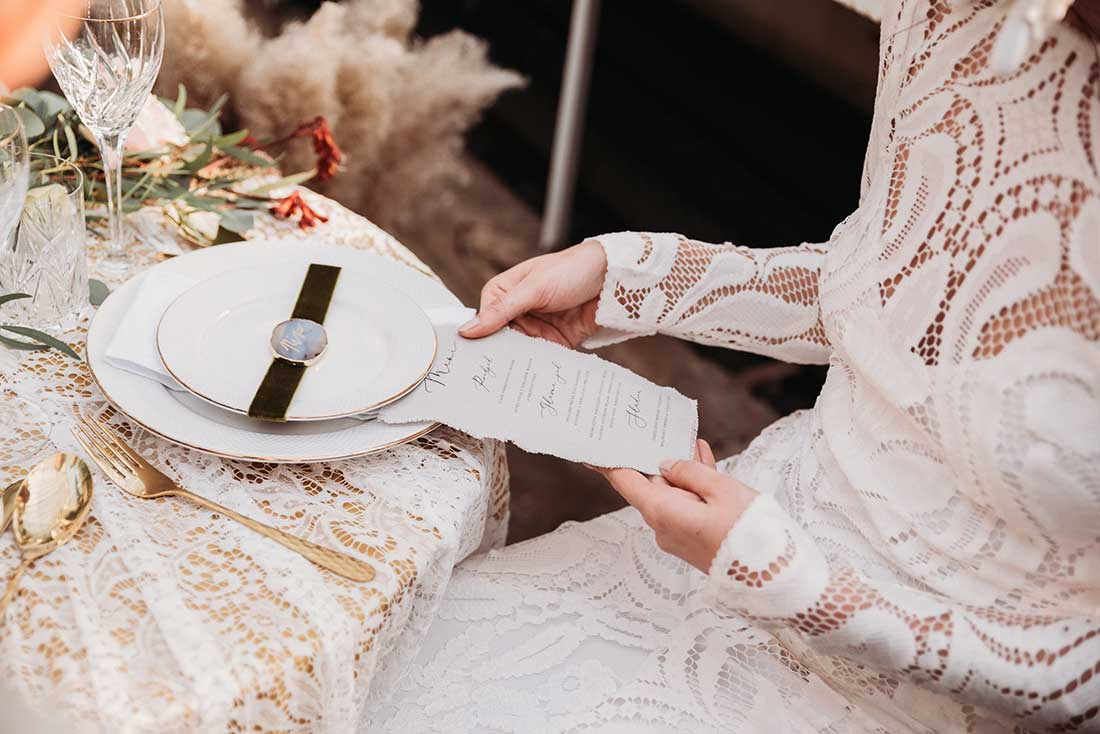 White plate with gold rim, stone name card and wedding menu on linen for boho table setting