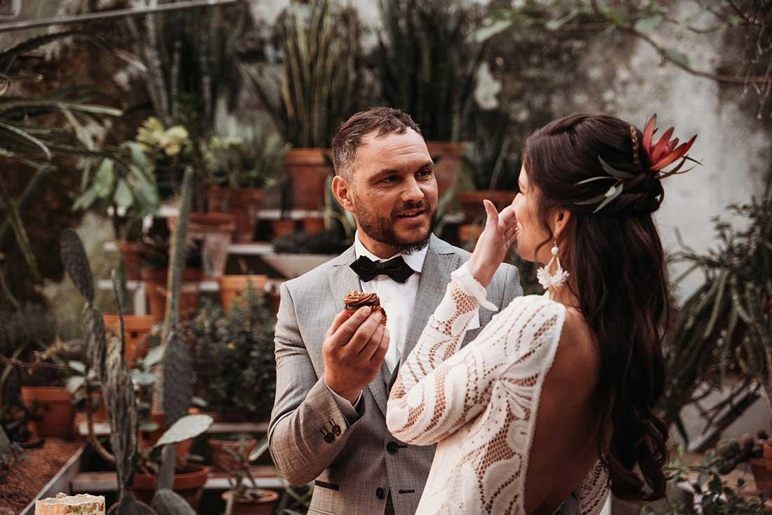 Newlyweds eat wedding cake in a greenhouse in Sežana Botanical Garden