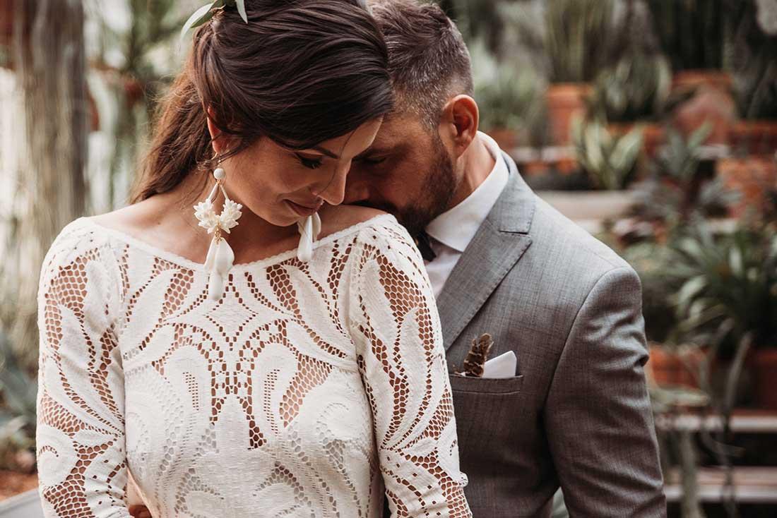 Wedding photo shooting - groom kissed the bride on her shoulder