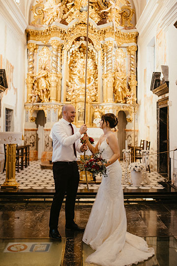 The bride and groom ring the wishes bell at the church on Lake Bled