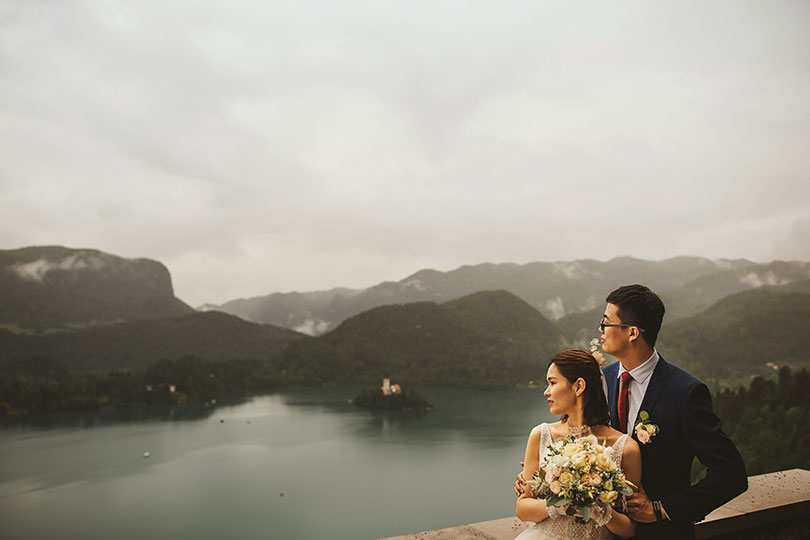 Newlywed couple enjoys breathtaking view from Bled castle during their Bled Wedding