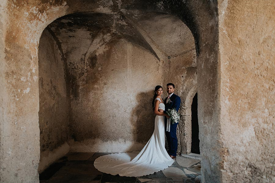 Bride in a stunning lace wedding dress holds her groom on the Lake Bled Castle small intimate terrace