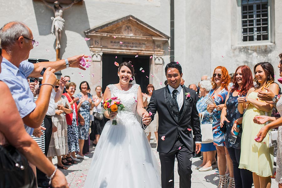 Top Lake Bled Wedding planner Petra Starbek organized a perfect bride and groom exit from the lake bled island church with fresh petals and live music