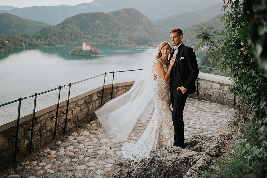 Bride and groom are standing on the Lake Bled Castle terrace with a lake bled island view and they are kissing during wedding photo shooting