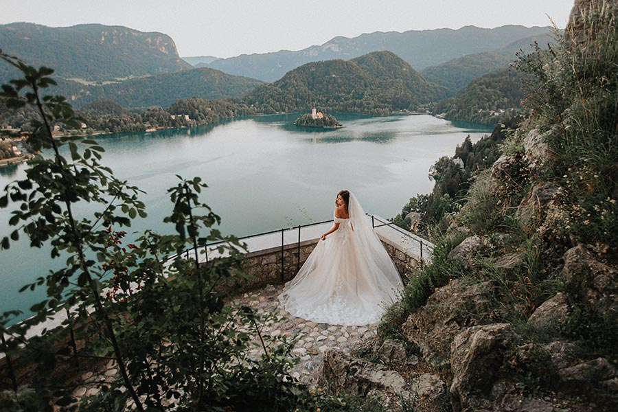 Bride in a stunning white wedding dress with lace and pearls stands at the Lake Bled Castle terrace with a lake bled island view