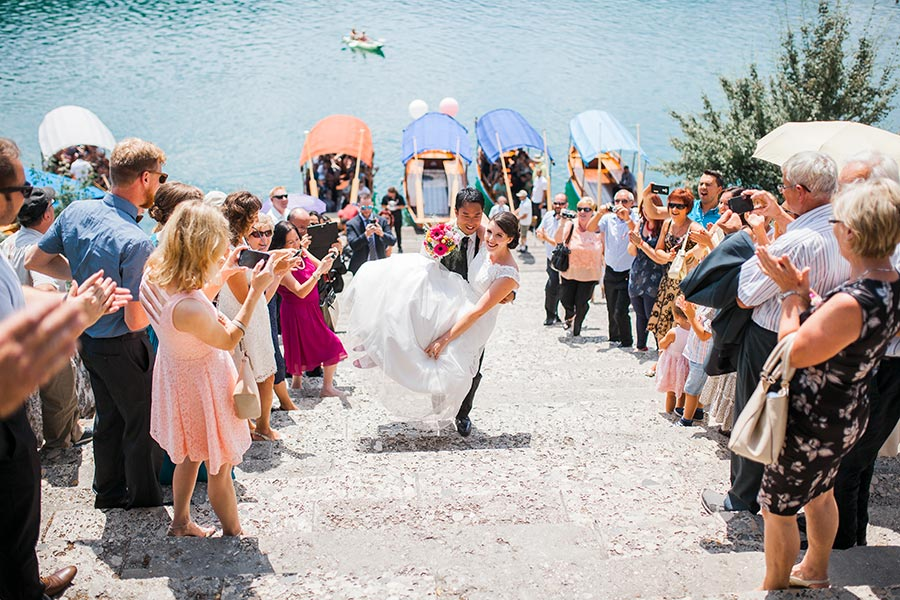The wedding guests and the lake bled wedding planner Petra Starbek are looking at the happy groom who carries the bride in his hands on the Lake Bled island stairs