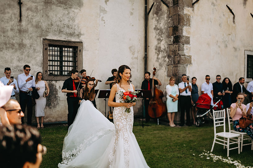 Top wedding planner Petra Starbek helping beautiful bride with wedding dress