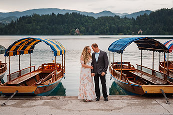 Couple stands in front of Lake Bled for their wedding anniversary