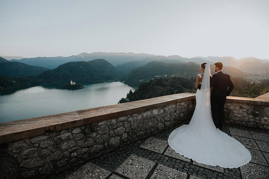 Bride and Groom are looking at the amazing lake bled island from a Lake Bled terrace