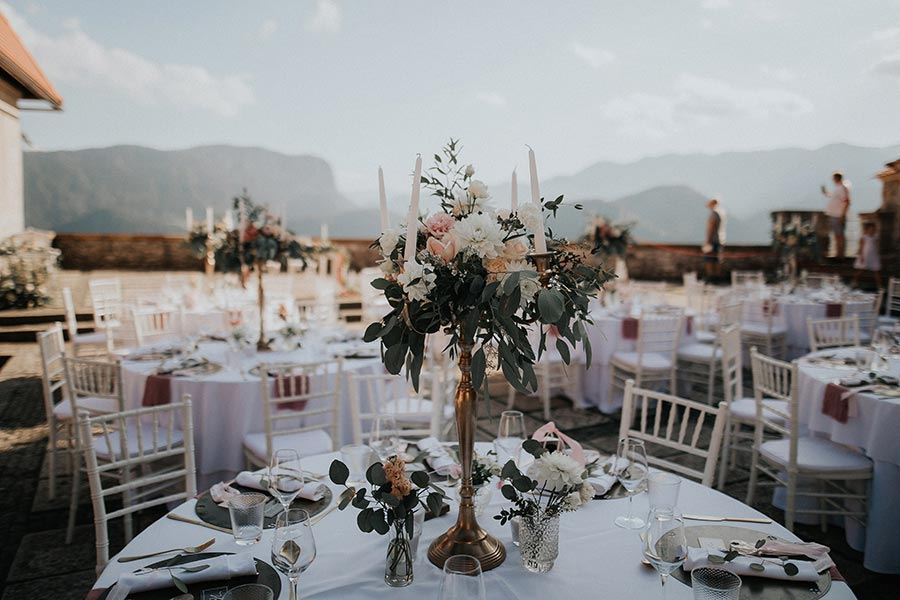 Wedding setting at Lake Bled castle with gold candelabras, flowers, candles, and small flower on a table