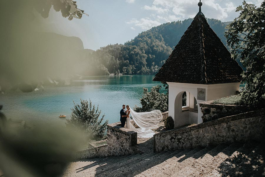 A stunning bride with a long veil and the groom in a black suit are taking photos on Lake Bled island after their bespoke personal wedding planner from the Petra Starbek wedding team