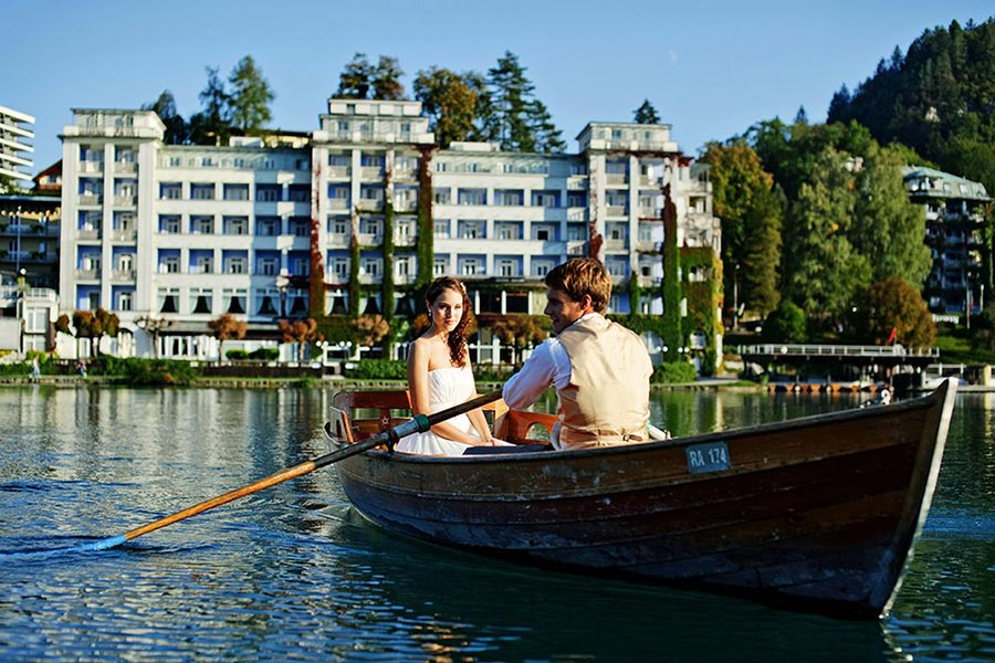 Bride and groom in a boat in front of Lake Bled wedding venue Grand hotel Toplice