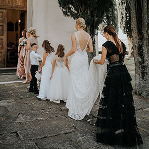 Wedding planner Petra Starbek helping a bride with her train on her marriage in Slovenia