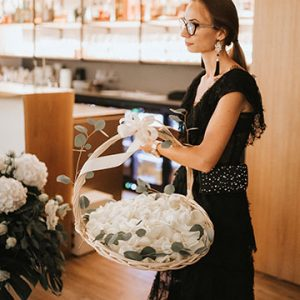 A Lake Bled wedding planner Petra Starbek with a basket full of flowers petal