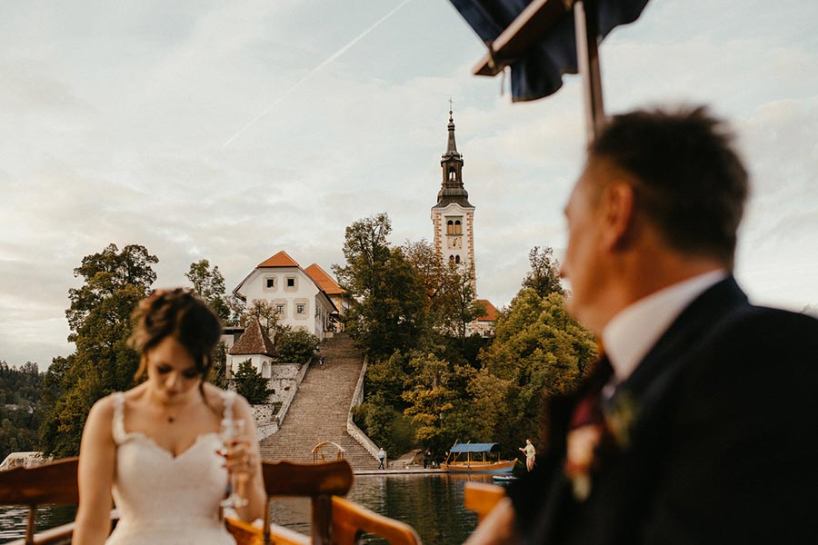 Newlywed ride a pletna boat to the Lake Bled Island to Lake Bled Island church where they will make a wish will have their wish come true