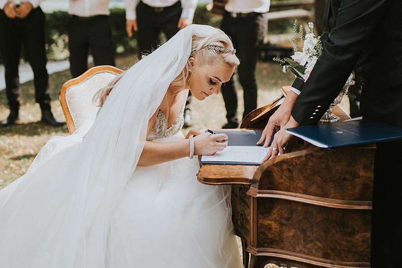 Happy bride is signing her wedding certificate at Lake Bled Vila