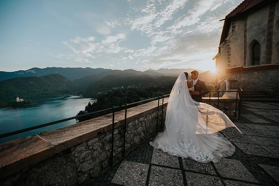 Bride in bespoke wedding dress and groom are taking photos during sunset on the Lake Bled Castle terrace with a lake bled island view
