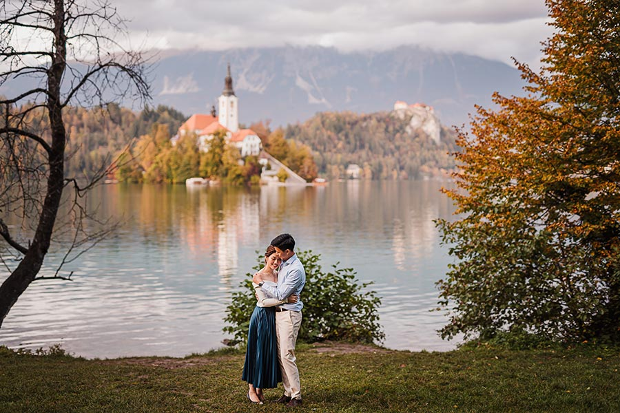 Man and woman hold eachother during walking around Lake Bled