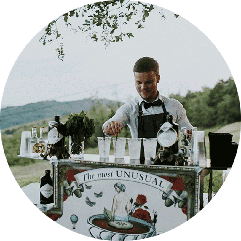 During the wedding reception, a barman makes a gin tonic and other cocktails at Lake Bled wedding venue.
