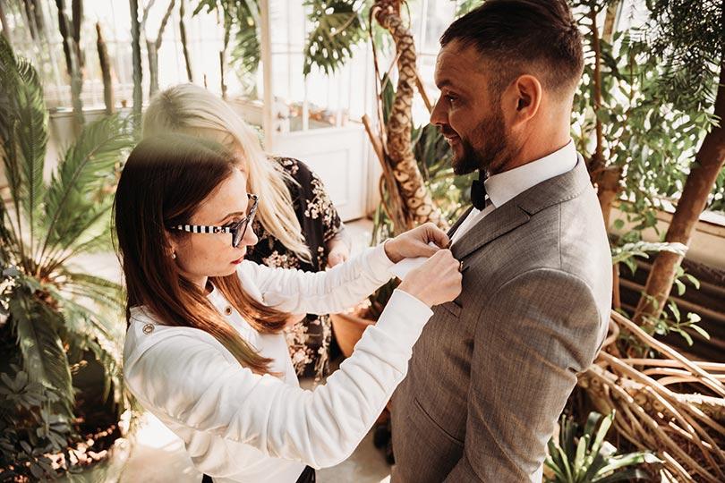 Certified wedding planner Petra Starbek helps groom with his flower boutonnier